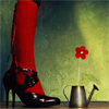 meloukhia: Red stockinged legs in black heels, standing next to a watering can with a red flower. (calla lily)