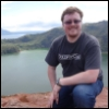 mark: A photo of Mark kneeling on top of the Taal Volcano in the Philippines. It was a long hike. (Default)