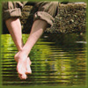 pocketmouse: Bare feet dangling over rippling water, reflecting the greenery around (feet-water)