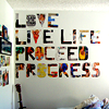 seeitbloom: text icon saying the words in the keyword section; letters are colorful cutout decorations on a wall (love live life proceed progress)