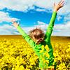 wendelah1: A woman holding up her arms, in a field of yellow flowers (Joy)