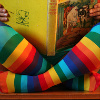 feuille: Person reading with rainbow socks on (rainbow legs with book)