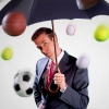 oneill: Onion SportsDome - Mark Shepard holds an umbrella as baseballs, basketballs, soccer balls, and tennis balls rain down (It Is Fashionable)