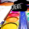 zellieh: A tray of brightly coloured paints and a paintbrush. Text: CREATE (writing: create)