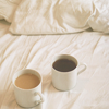 sarken: two mugs of coffee on a bed with white sheets ([misc] right next to her coffee)