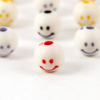 lienne: Several beads painted with smiling faces. (emotion: friendly)