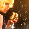 teaotter: a blonde woman sings into an old-fashioned microphone on a dark stage (Bombshell)