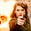 azarsuerte: Peggy Carter (Hayley Atwell) pointing a gun at the camera while a car explodes behind her (MCU - Peggy Carter)