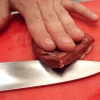 rydra_wong: Fingers holding down a piece of meat (heart) as it's cut with a knife, on a bright red surface. (food -- a slice of heart)