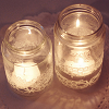 majoline: two candles flickering in separate mason jars (candles in jar)