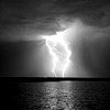 seeitbloom: black and white photo of dark clouds over a large body of water and huge, bright lighting striking (storm coming in)
