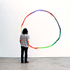 seeitbloom: person standing in an empty room staring at a white wall with a painted, colorful circle on it (beautiful minimalism)