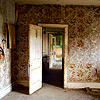 seeitbloom: photograph of an old, rundown room with a door open and a view into the hallway (abandoned)