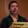 "rmc28: Rachel speaking at a lectern with microphone and part of the slogan ""Stronger Economy Fairer Society"" in shot (libdem, speaking)"