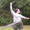scheherezhad: woman hula hooping in a grey top and green shorts (hooper)