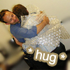 jesse_the_k: Human embraces another who's encased in bubble wrap (hug gently)