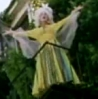 vass: Amanda Palmer in a long dress and white wig, on a balcony, gesturing with both arms up (Operatic)