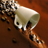 green_dreams: A tilted picture of a coffee cup spilling beans. (hang on to your cups)