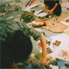 exchangediary: color photo of two people amidst scraps of paper and crafting supplies (Craft city)