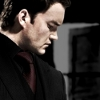 bethmccombs: Closeup of Ianto Jones dressed in black on a black background with an open door in the distance (Torchwood - Ianto Jones - Black)