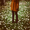 rainfall: A girl stands in the midst of fallen leaves. You can't see her face. (fallen leaves)