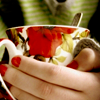 rainfall: A pair of hands holding an ornate teacup. The red fingernails and green shirt match the teacup's design. (teacups)