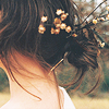 fascination: A picture of a woman from the back, with small blossoms in her brown hair. (Fancy.)