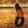 darwin: A girl sitting on a tyre swing. (Swing.)