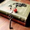 meloukhia: A skeleton key on a string of beads, laid out over a book (Key rosary)