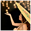 meloukhia: A person holding a parasol in the evening, reaching up as though to touch a strand of lights hanging in the air (Parasol by night)