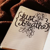 """alee_grrl: Sheet of paper with decoratively written """"just breathe"""" on dark cloth background (just breath)"""