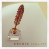 calissa: Photo of Swarovski crystal & gold figurine of inkpot and quill sitting on a page that says 'create every day' (Writing)