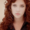 dance_of_fire: picture of a pale woman with big eyes and curly red hair wearing black leather and making a doomface. (Default)