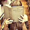 katmarajade: woman holding a large, old book very close to her face (reading)