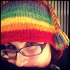 tajasel: photo of me with a rainbow hat and big scarf on (Default)