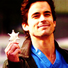 anoyo: Neal smiling and holding a Sheriff's badge. (wc neal badge)