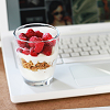 fascination: A yoghurt parfait resting at the edge of a white laptop. (Computing & yoghurt.)