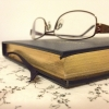 calissa: A low angle photo of a book with a pair of glasses sitting on top. (Mt TBR)
