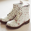 darwin: A pair of white Doc Martens covered with pink flowers. (Floral boots.)