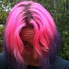 samvara: woman peering through bright pink hair (pink hair)