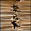 kate_nepveu: closeup of two stacks of paper (buried under piles of work)