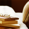 branchandroot: stack of books by arm chair (book love)