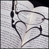 helgatwb: glasses on an open book, the shadow forms a heart (glasses)