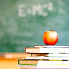 skieswideopen: A stack of books topped by an apple in front of a blackboard (academic)