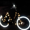 darkemeralds: A bike in the dark, decorated with white lights, its wheel rims bright reflective white in the flash (Christmas)