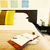 celli: a bed and bedside table, with a journal lying open on the bed (home)