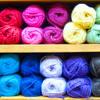 alexseanchai: Yarn in rainbow colors stacked on shelves (rainbow yarn)