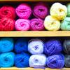 alexseanchai: Yarn in rainbow colors stacked on shelves (rainbow yarn)
