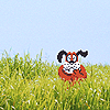 tablesaw: The pixelated dog from Duck Hunt, emerging from a real field of tall green grass beneath a clear blue sky. (Duck Hunt)
