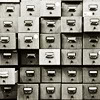 tears_of_nienna: black-and-white image of a card catalog with drawers opened at various degrees (Default)